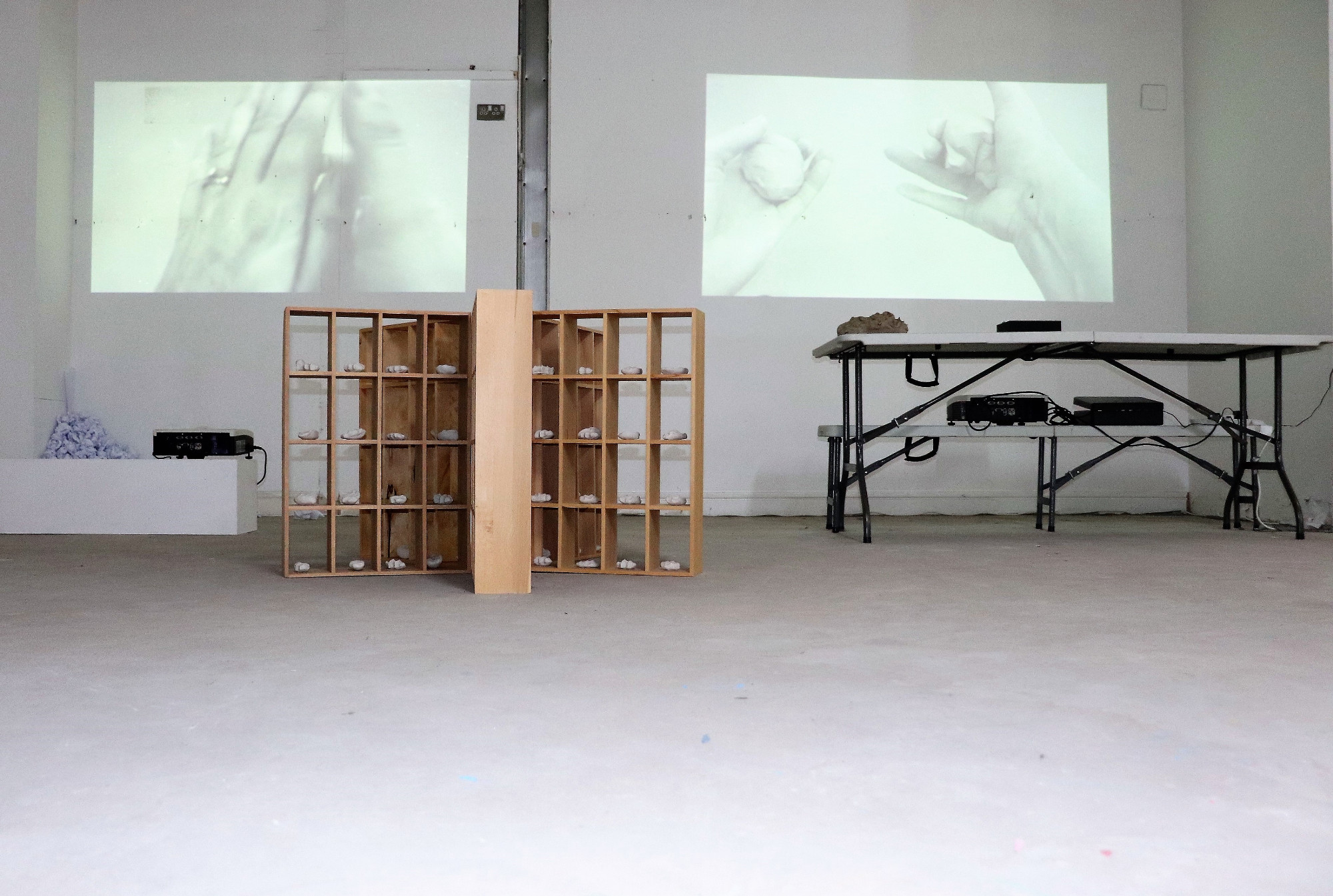 'Holding on' 2019, Installation - Ceramics, paper, clay, video projection, wooden shelving - Sarah Strachan